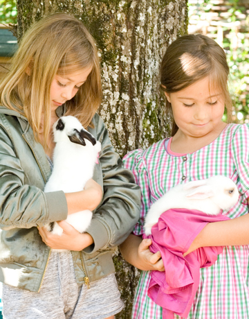 Mädchen mit Häschen im Garten