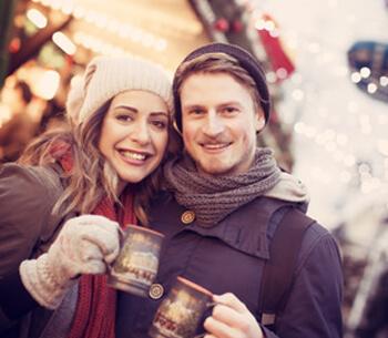 Winterurlaub in Garmisch-Partenkirchen – Paar auf Adventsmarkt mit Glühwein
