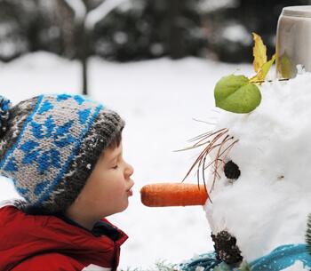 Winterurlaub in Garmisch-Partenkirchen – Kind mit Schneemann
